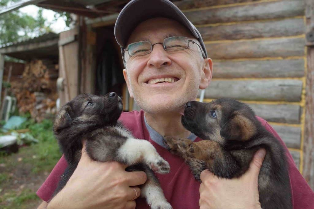 man holds two puppies in his arms