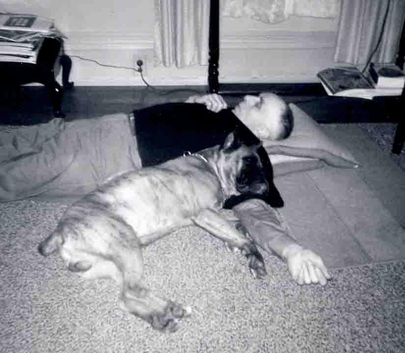 Grandfather and dog sleeping on floor.